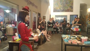 Image features Fox Smith in her Mad Moxxi costume surrounded by patiently waiting event participants as she conducts a drawing for the auction.